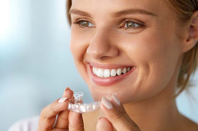 invisalign-woman-holding-aligners